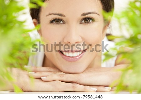 Health spa nature concept studio portrait of a beautiful young woman or girl resting on her hands smiling through natural green leaves - stock photo