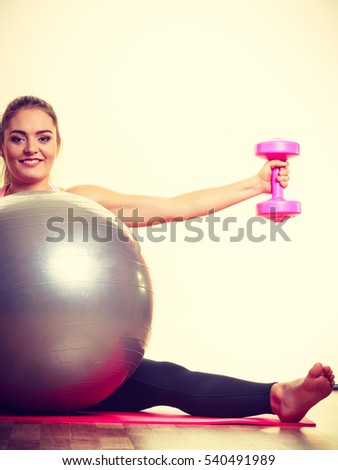 Health sport muscles activity concept. Cheerful female exercising. Young fit lady during workout lifting dumbbells practicing with fitness ball.
