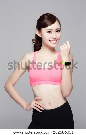 Health sport woman wearing smart watch device with touchscreen doing exercises isolated on gray background, asian beauty - stock photo