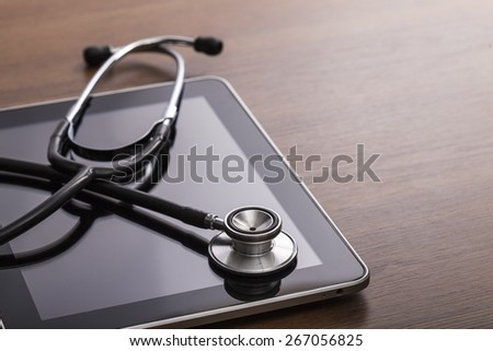 Health. Studio macro of a stethoscope and digital tablet with shallow DOF evenly matched abstract on wood table background copy space - stock photo