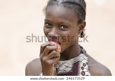 Health Symbol: Beautiful Young African Girl Biting A Healthy Apple - stock photo