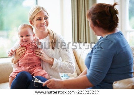 Health Visitor Talking To Mother With Young Baby - stock photo