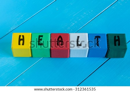 Health - word on children's colourful cubes or blocks. Colourful wooden background. - stock photo