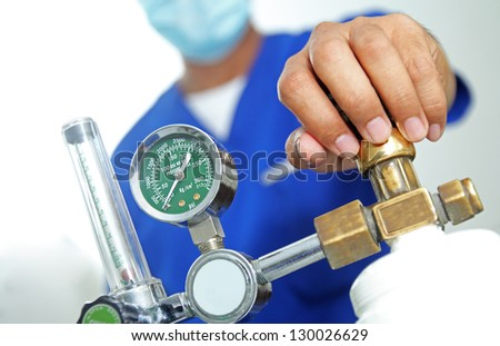 Health worker checking an oxygen tank. - stock photo