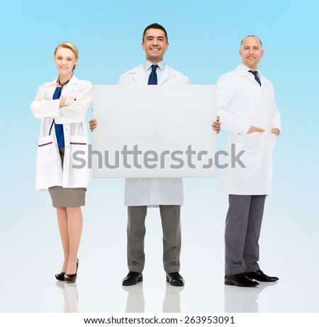 healthcare, advertisement, people and medicine concept - group of smiling doctors holding white blank board over blue background - stock photo