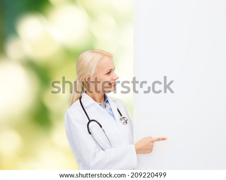 healthcare, advertisement, people and medicine concept - smiling female doctor with stethoscope showing something over natural background - stock photo