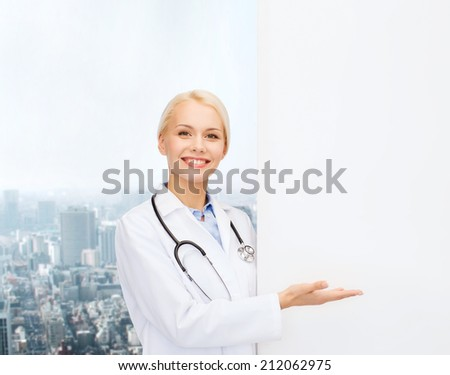healthcare, advertisement, people and medicine concept - smiling female doctor with stethoscope showing something over city background - stock photo