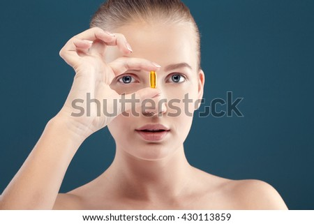 healthcare and beauty concept - lovely woman with omega 3 vitamins. Selective focus on capsule.