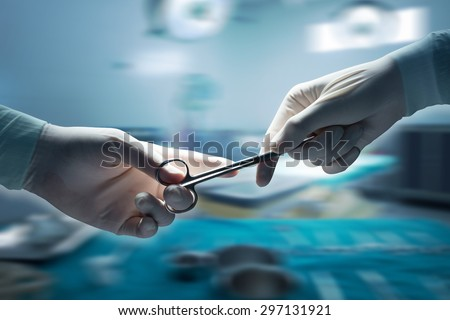 healthcare and medical concept , Close-up of surgeons hands holding surgical scissors and passing surgical equipment , motion blur background. - stock photo