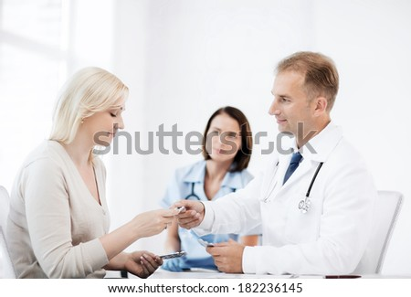 healthcare and medical concept - doctor giving tablets to patient in hospital - stock photo
