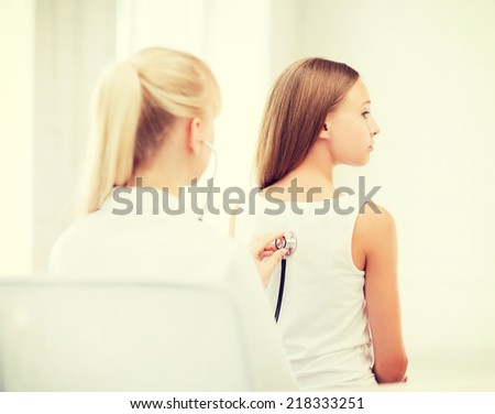 healthcare and medical concept - doctor with stethoscope listening to child back in hospital
