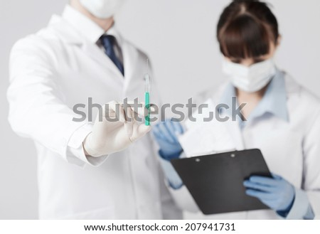 healthcare and medical concept - doctors with syringe - stock photo