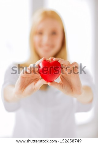 healthcare and medical concept - female doctor with heart