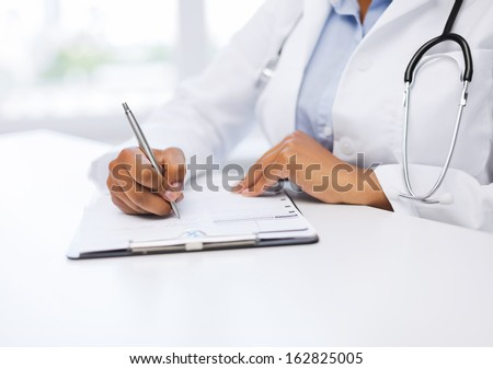 healthcare and medical concept - female doctor writing prescription - stock photo