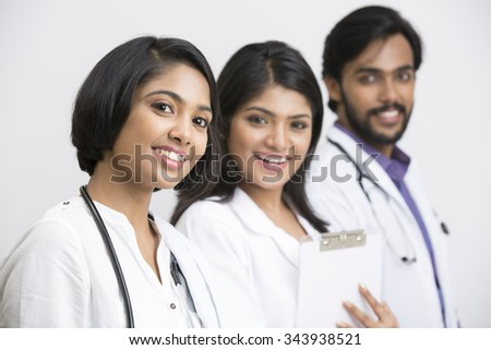 healthcare and medical concept - picture of three young Indian attractive doctors on white background. - stock photo