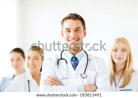 healthcare and medicine concept - attractive male doctor in front of medical group in hospital - stock photo