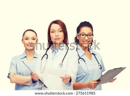 healthcare and medicine concept - calm female doctor adn nurses with clipboard and stethoscope giving prescription - stock photo
