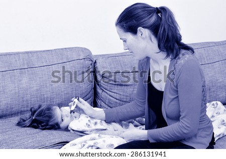 Healthcare and medicine concept - Caring mother taking care of her ill girl child with thermometer in mouth (BW) - stock photo