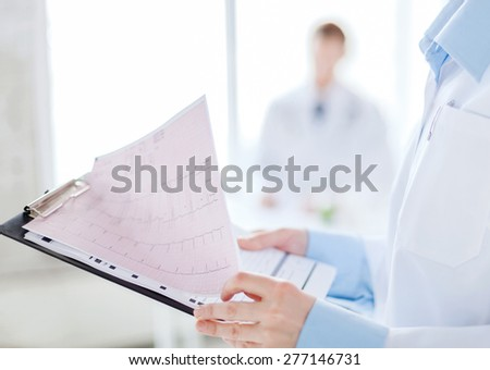 healthcare and medicine concept - close up of female holding clipboard with cardiogram - stock photo