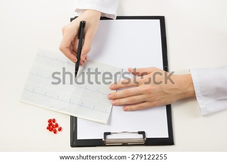 Healthcare and medicine concept - doctor with medical clipboard and red pills analyzing cardiogram. Top view - stock photo
