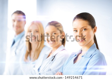 healthcare and medicine concept - female doctor in front of medical group - stock photo