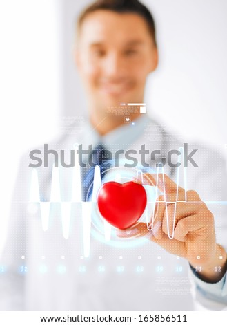 healthcare and medicine concept - male doctor with heart and cardiogram - stock photo