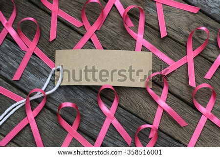 healthcare and medicine concept. pink breast cancer awareness ribbon on wood table.