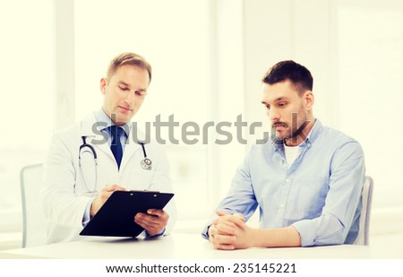 healthcare and medicine concept - serious doctor with clipboard and patient in hospital - stock photo