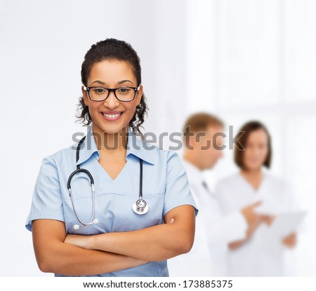 healthcare and medicine concept - smiling female african american doctor or nurse in eyeglasses with stethoscope - stock photo
