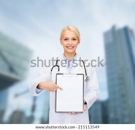 healthcare and medicine concept - smiling female doctor with stethoscope pointing finger to clipboard and blank page - stock photo