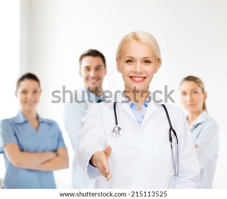 healthcare and medicine concept - smiling female doctor with stethoscope ready to shake hands - stock photo