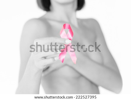 healthcare and medicine concept - womans hand holding pink breast cancer awareness ribbon - stock photo