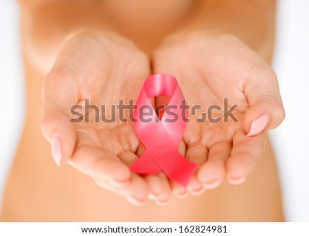 healthcare and medicine concept - womans hands holding pink breast cancer awareness ribbon - stock photo