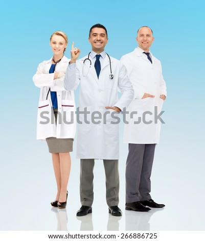 healthcare, announcement, people and medicine concept - group of smiling doctors in white coats pointing finger up and warning over blue background - stock photo