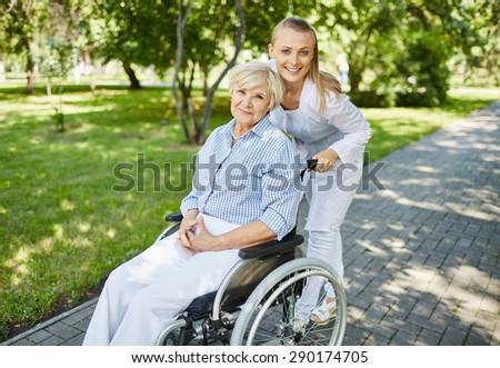 Healthcare assistant and aged woman in a wheelchair looking at camera during walk in park