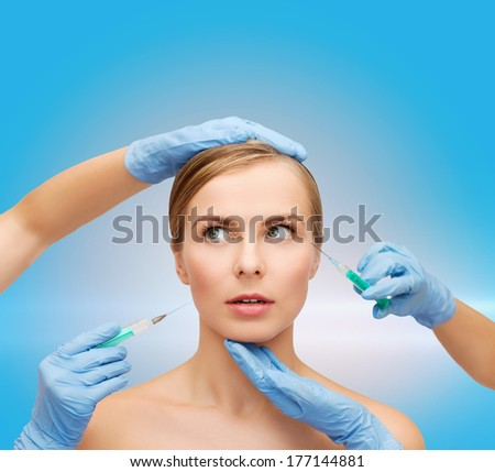 healthcare, beauty and medicine concept - beautiful scared woman face with closed eyes and beautician hands with syringe - stock photo