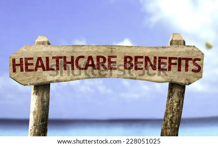Healthcare Benefits wooden sign with a beach on background - stock photo