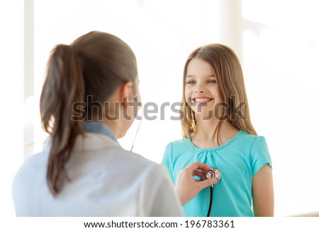 healthcare, child and medical concept - female doctor with stethoscope listening to child chest in hospital - stock photo