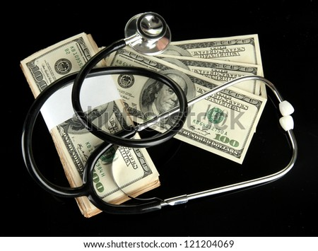 Healthcare cost concept: stethoscope and dollars isolated on black