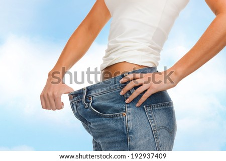 healthcare, diet and fitness concept - close up of female showing big jeans - stock photo