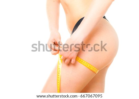 Healthcare fit and diet concept. Perfect slim female with young beautiful body dressed in black neutral lingerie with a measuring tape isolated on a white background. Detailed closeup studio shot.