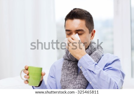 healthcare, flu, people, rhinitis and medicine concept - ill man blowing his nose with paper napkin and drinking tea at home - stock photo