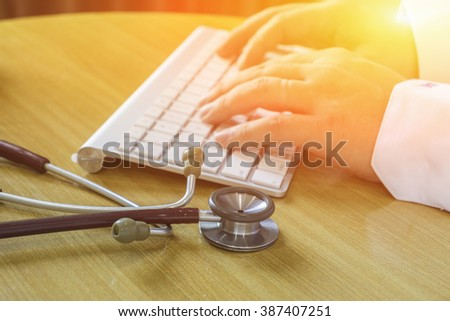 healthcare, hospital and medicine concept - male doctor typing on the keyboard,Doctor type keyboard with stethoscope,selective focus,vintage color. - stock photo