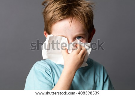 healthcare learning - cute little child with red hair and blue eyes hiding with a tissue to clean his nose from a cold or having hay fever, grey background studio - stock photo