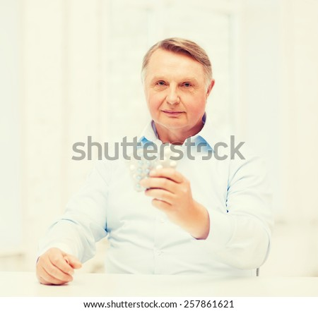 healthcare, madicine, pharmacy and elderly concept - old man with pack of pills - stock photo