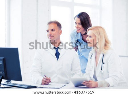 healthcare, medical and technology - group of doctors looking at computer on meeting - stock photo