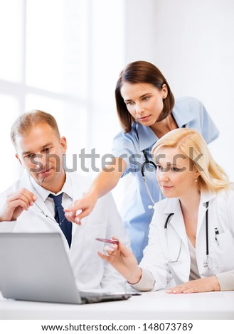 healthcare, medical and technology - group of doctors looking at laptop on meeting - stock photo