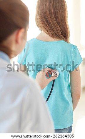 healthcare, medical exam, people, children and medicine concept - close up of girl and doctor with stethoscope listening to heartbeat - stock photo