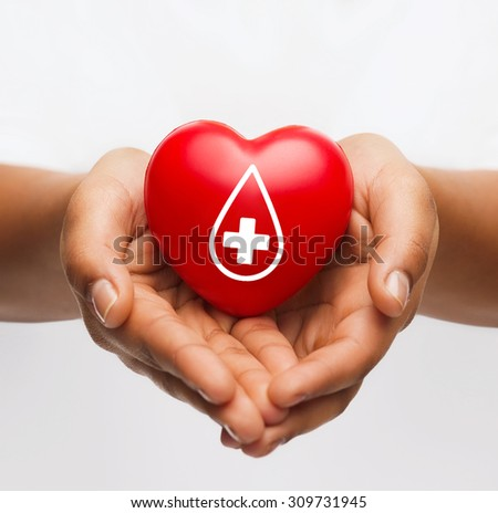 healthcare, medicine and blood donation concept - african american female hands holding red heart with donor sign - stock photo
