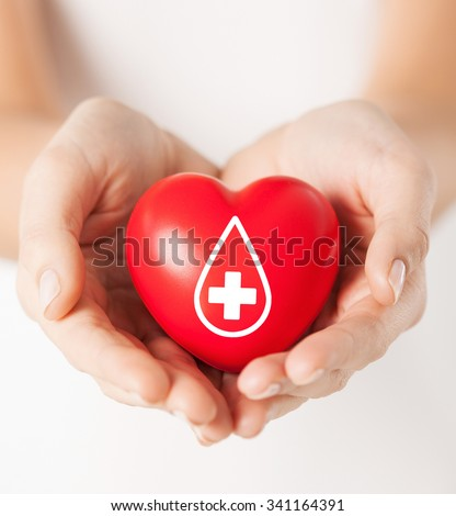 healthcare, medicine and blood donation concept - female hands holding red heart with donor sign - stock photo